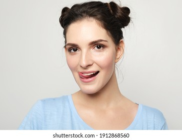 lifestyle, fashion, emotion and people concept: young brunette woman dressed casually making faces at camera, sticking out her tongue. Positive girl having fun over grey background.