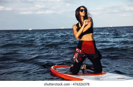 Lifestyle fashion portrait of active women enjoy Watersport at her vacation,Kitesurfing holidays worldwide,sport girl,enjoy Kite Surfing School,shows her sexy body,surf girl.instructor of Windsurf