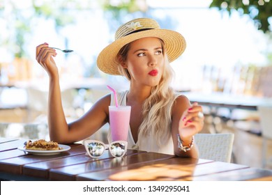 Lifestyle fashion portrait of charming girl eating apple strudel in cafe outdoors. Holding in her hand dessert spoon. Drinking milk shake, enjoying vacation. Wearing stylish straw hat, white t-shirt.
