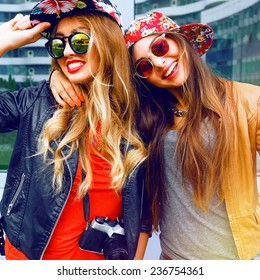 Lifestyle fashion portrait of happy stylish girls friends, hugs and enjoy travel time together, wearing hats and sunglasses holding vintage retro camera, bright colors positive emotions.