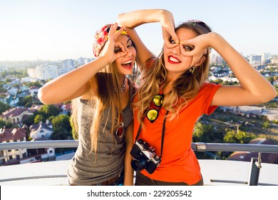 Lifestyle fashion portrait of two cheerful pretty best friends girls making funny faces and going crazy together, wearing bright clothes, holding retro camera and posing on the roof.