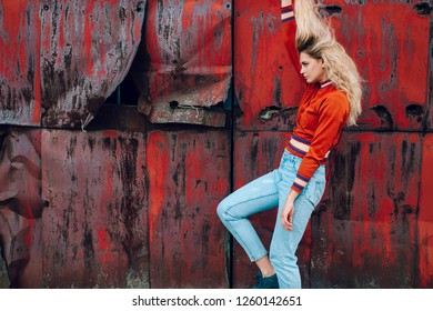 Lifestyle fashion portrait of young beautiful cute girl model.  Odd bizarre strange unusual cute naughty blonde babe posing on old rusty metal gate background. Nice looking woman in trendy clothes.