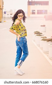 Lifestyle fashion portrait of a young beautiful girl posing on the street. Stylish woman wearing cute trendy outfit. Summer street female fashion