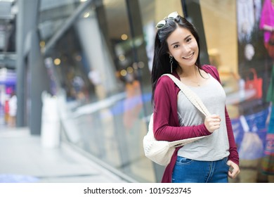 lifestyle fashion portrait of young stylish hipster Asia woman walking on the street, wearing cute trendy outfit