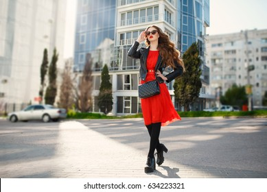 Lifestyle fashion portrait of young stylish woman outdoors wear trendy outfit - red flying dress black leather jacket. Vogue style model - bright makeup long curly hair at city street. Beautiful girl.