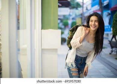 lifestyle fashion portrait of young stylish hipster Asia woman walking on street,wearing cute trendy outfit