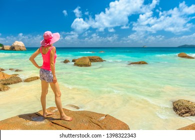 Lifestyle female in sunhat standing on a large granite boulder in popular Anse Lazio beach. Carefree woman looking turquoise Indian ocean on Praslin Island, Seychelles. Sunny beautiful sky.