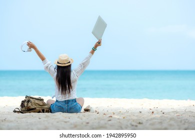 Lifestyle freelance woman using laptop working and relax on the beach. Asian people success and together your work pastime and meeting conference on internet in holiday. Business and Summer Concept