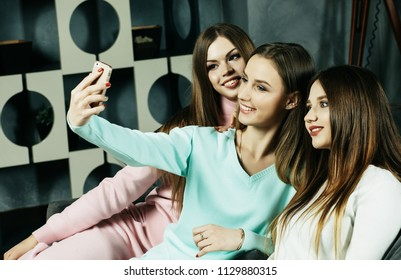 lifestyle, friendship, people  and technology concept - happy friends or teenage girls with smartphone taking selfie at home