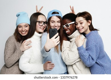 lifestyle, friendship, tehnology and people concept: five different nation girls dressed in casual wear make selfie with a smartphone over white background