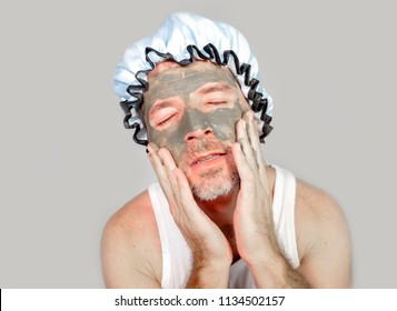 lifestyle funny portrait of happy weird man on shower cap looking to himself in bathroom mirror with green cream on his face applying facial mask skin care product smiling cheerful and fresh