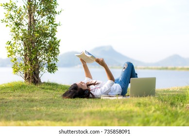 Lifestyle Girl enjoy listening music and reading a book and play laptop on the grass field of the nature park in the morning (greenery tone). Concept lifestyle