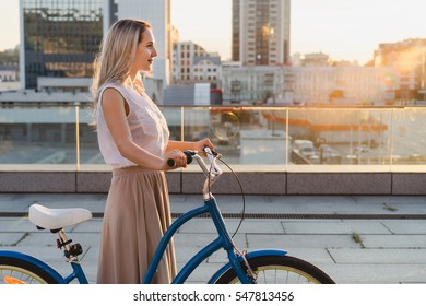 Lifestyle and health in the city. Active fashionable blonde woman with vintage bike on urban background at sunset. Copy space. Good day for a ride.