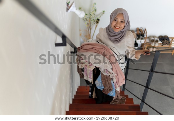 Lifestyle at home, cute malay woman doing routine housework by folding her laundry