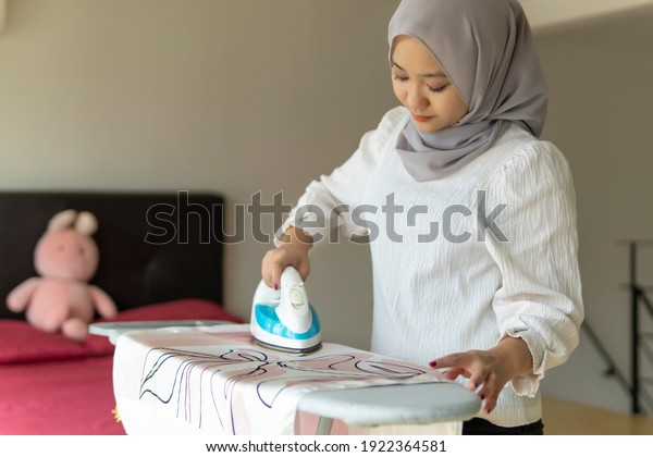 Lifestyle at home, cute malay woman doing routine housework by ironing clothes