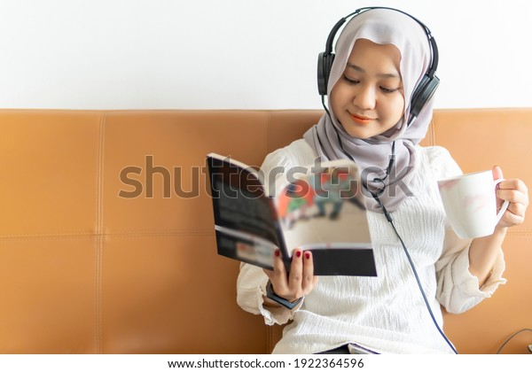 Lifestyle at home, cute malay woman at the sofa reading books
