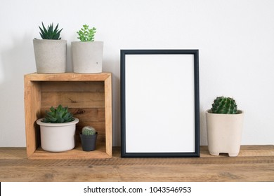 Lifestyle home decoration with mock up frame poster and cactus in pot on wooden table