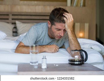lifestyle home portrait of young exhausted and wasted man waking up suffering headache and hangover after drinking alcohol at night party lying on bed sick and miserable still drunk