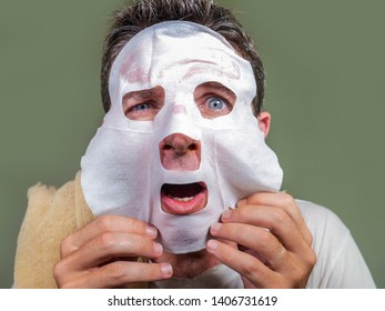 lifestyle home portrait of young funny and messy man applying beauty facial mask looking to the mirror surprised and horrified in skin care aging concept and male cosmetic face treatment