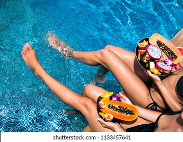 Lifestyle hot close up picture of two woman sitting near pool holding big plates with amazing sweet tasty tropical exotic fruits, amazing long legs, healthy Egan vegetarian lifestyle, diet concept.