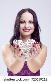 Lifestyle Ideas. Portrait of Mature Caucasian Woman Posing with Wicker Heart as Love Symbol. Against White. Vertical Image