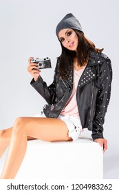 Lifestyle Ideas. Sexy Sensual Tanned Caucasian Brunette in Black Leather Jacket and Warm Hat Posing With Old School Film Photocamera. Against White.Vertical Image
