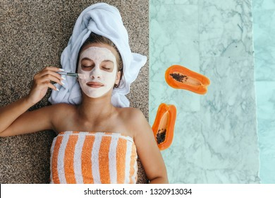 Lifestyle image of 12-14 years old teen applying organic fruit facial mask with papaya. Top view photo of teenage girl wrapped in towel doing anti blemish face treatment by the pool side.