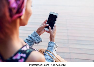 Lifestyle image of black woman chatting by smartphone . Watching video during coffee break. Close up of hands.