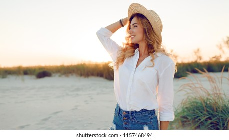Lifestyle Image of carefree  traveling smiling woman in white blouse  and straw hat spending her leisure time on the beach . Summer mood.