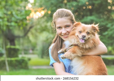 Lifestyle image of cute young woman holding dog and smiling. Loving dog in his owner's arms in the park. Concept of caring for a pet and animal adoption. Image with copy space for adding text or quote