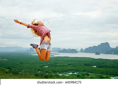 Lifestyle image of happy young traveling woman jumping carefree on nature background. In the mountains. Wearing stylish short shorts and checkered shirt. Freedom and happiness concept. In motion