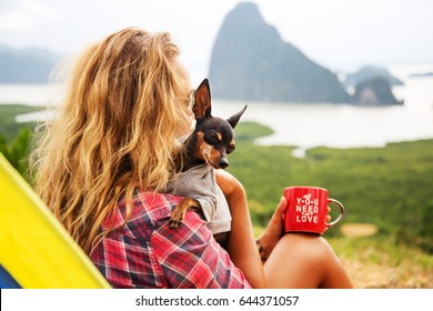Lifestyle image of happy young woman sitting with small cute dog near a tent in the mountains. Drinking tea. Wearing stylish checkered shirt. Freedom and happiness concept. Tourism and adventure
