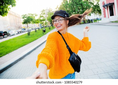 Lifestyle image of playful girl fooling around in sunny evening city. Windy hairs. Happy emotions.