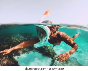 Lifestyle image of pretty girl snorkeling in full-face snorkeling mask undersea. Underwater swimming in ocean. Tropical vacation activity snorkel. Active seaside vacation. Water sport in tropical sea