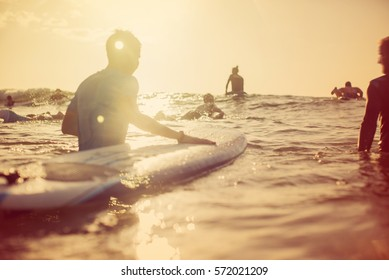 Lifestyle image of unrecognizable surfers going out to surf