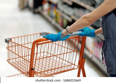 Lifestyle image. Woman with shopping cart and wearing medical blue glove in grocery store. Protect coronavirus.