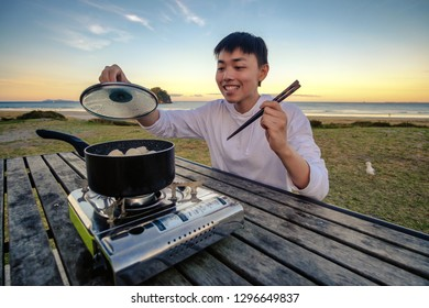 Lifestyle image of young happy asian man eating hot pot stove on a table outdoor along beach. Leisure activity image of chinese person holding chopsticks ready to eat a meal outside.