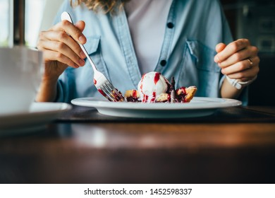 Lifestyle image of young woman eating cherry pie with scoop of ice cream. Close-up of female's hand holding a fork next to dessert sitting at table in cafe.