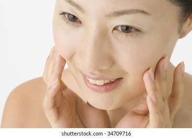 LIFESTYLE IMAGE-close-up shot of a Japanese woman's face doing her skin care