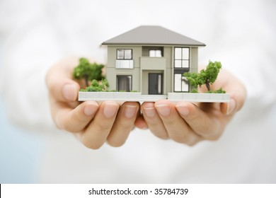 LIFESTYLE IMAGE-the model house with woman's hands isolated on white