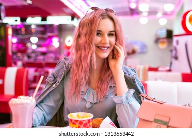 Lifestyle indoor image of stylish young pretty woman with wavy unusual pink hairs and natural make up, wearing cute blue dress and denim jacket, enjoy her tasty American dinner.