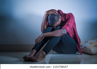 lifestyle indoors shady portrait of young sad and depressed black african American woman sitting at home floor feeling desperate and worried suffering pain and depression in dramatic light
