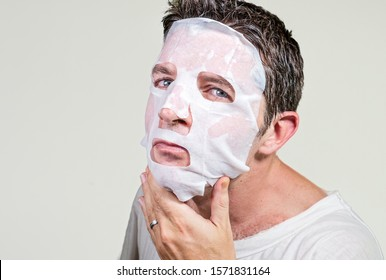 lifestyle isolated background portrait of young weird and funny man at home trying using paper facial mask cleansing applying anti aging beauty treatment in hilarious face expression