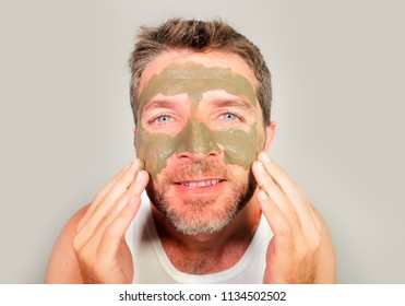 lifestyle isolated portrait of young attractive and happy man looking to himself in bathroom mirror with green cream on his face applying facial mask skin care product smiling cheerful and fresh
