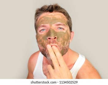 lifestyle isolated portrait of young attractive and happy man with green cream on his face applying facial mask sending kiss to his reflection in mirror feeling conscious in male cosmetics concept