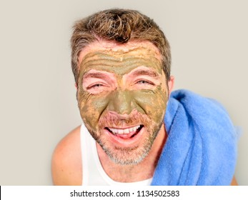 lifestyle isolated portrait of young attractive and happy man with bathroom towel  laughing of himself in the mirror with green cream on his face applying facial mask and male skin care cosmetics