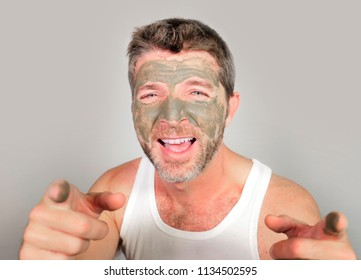 lifestyle isolated portrait of young attractive and happy man  laughing looking at himself in the mirror funny with green cream on his face applying facial mask and male skin care cosmetics