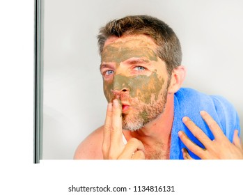 lifestyle isolated portrait of young attractive and happy man with bathroom towel  smiling with green cream on his face applying facial mask sending kiss to his reflection in mirror feeling conscious