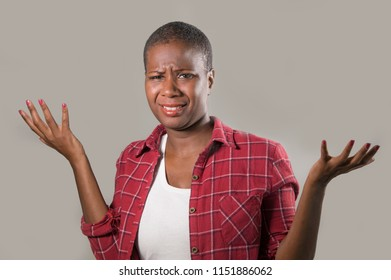 lifestyle isolated portrait of young pretty and unhappy black afro American woman gesturing with hands and face expression as if unable to understand or asking for explanations