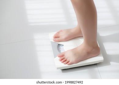 Der Lebensstil mit Frauenbein steht für eine Diät mit barfuß, Nahaufnahme eines kleinen Mädchengrundes zur Gewichtsabnahme für Nahrungskontrolle und Ernährung, Gesundheitsversorgung und Wellness-Konzept.